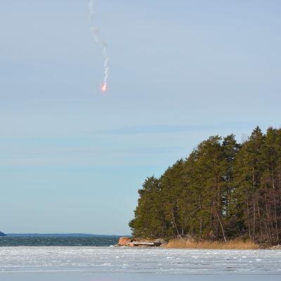 En nödraket dalar ner mot is och öppet vatten från en klar himmel.