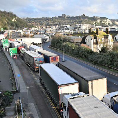 Kuorma-autoja on pitkässä jonossa maantiellä kohti satamaa.