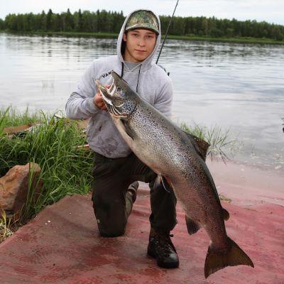 Veikka Körkkö poseeraa juuri saamansa lohen kanssa Tornionjoen rannalla