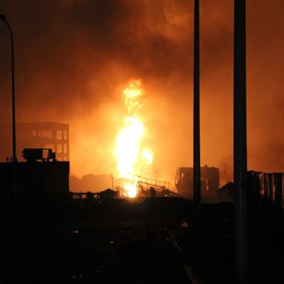 Flammor efter explosionen i Tianjin, Kina.