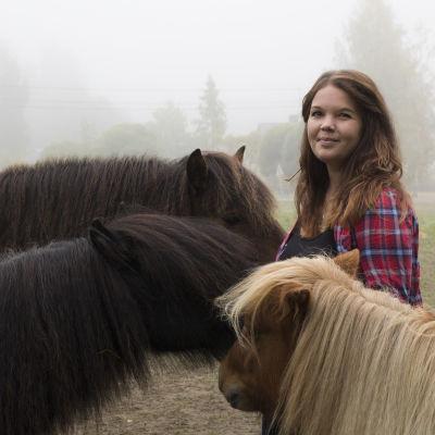 Sabina Granbacka tillsammans med sina tre hästar. Alla hästar står runt henne, med ansiktet mot henne.