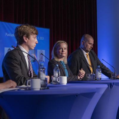Vasemmalta alkaen Kristiina Ilmarinen Sakari Puisto Riikka Purra ja Ossi Tiihonen seisovat sinisten pystypöytien takana puheenjohtajaehdokkaiden paneelissa. Riikka Purra katsoo kohti kameraa.