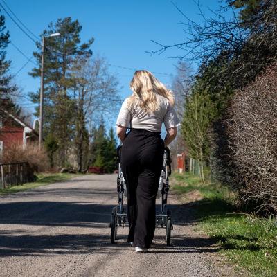En kvinna promenerar med barnvagn på en grusväg.