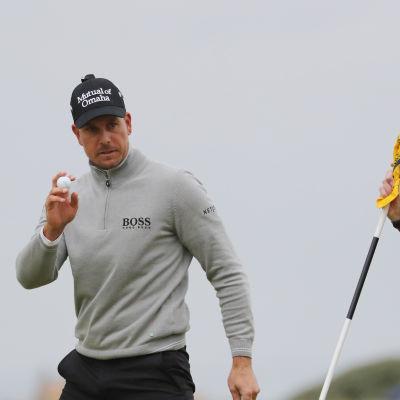 Henrik Stenson med en golfboll i handen och en gul flagga bredvid sig.