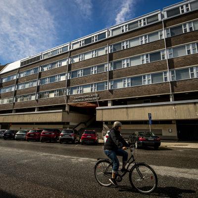 En byggnad i tegel och betong, en person cyklar förbi byggnaden.