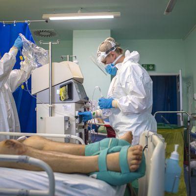 Henkilökunta valmistelee hoitolaitetta, sairaalasängyllä makaavasta potilaasta näkyvät jalat