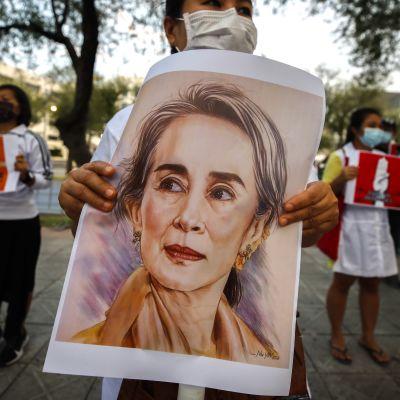 Demonstrant som håller upp en affisch av Myanmars ledare Aung San Suu Kyi