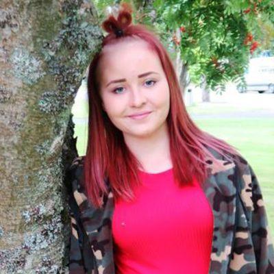 Tyttö nojaa puunrunkoon.