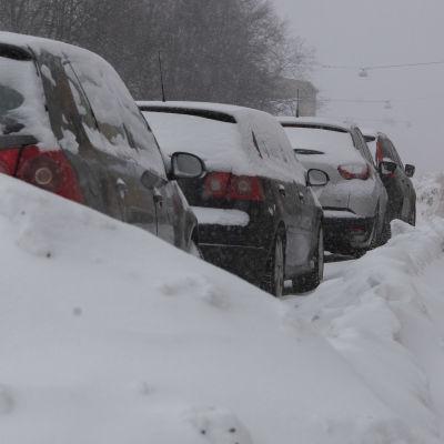 Bilar parkerade vid snövall