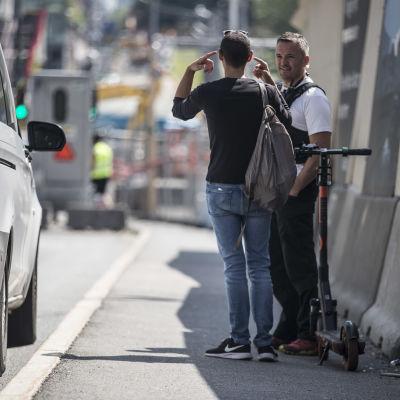Poliisi puhuu sähköpotkulaudan vieressä seisovan miehen kanssa.