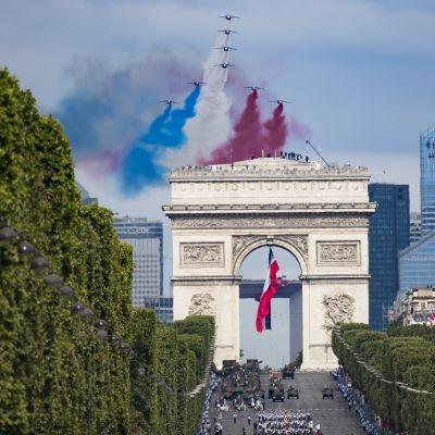 Riemukaaren yllä lentävät suihkuhävittäjät tekevät taivaalle sini-valko-punaisen kuvion. Kadulla marssii sotilasparaati.