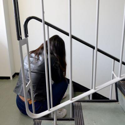 Nuori nainen istuu rappukäytävässä.