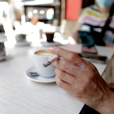 En kvinna som röker på ett café i La Coruna, i galicien, Spanien 13.8.2020.