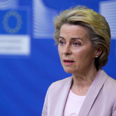 Ursula von der Leyen står och talar i en mikrofon framför en blå vägg med EU-flagga.