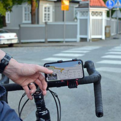 Pyörän tangossa on puhelin, jossa auki Crowdchupa-mobiilisovellus.