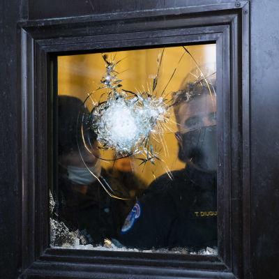 Polis tittar ut genom ett krossat fönster.