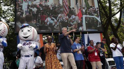 New Yorks borgmästare talar i mikrofon. Brevid honom står New Yorks baseballlags maskottar.
