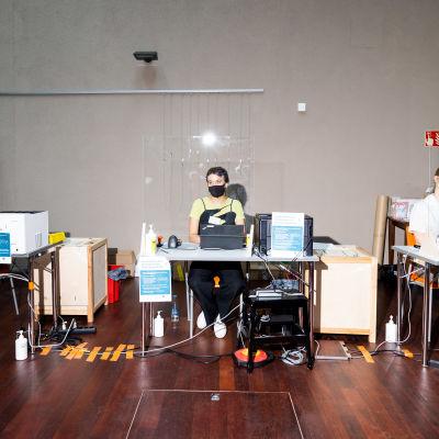 Kolme vaalityöntekijää istuu omilla äänestyspisteikllään rivissä. Pöytien väleissä on vaaliuurnat, takana seinä.