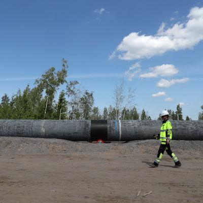 Keltaiseen huomioliiviin ja kypärään pukeutunut työntekijä kävelee kaasuputken vieressä.