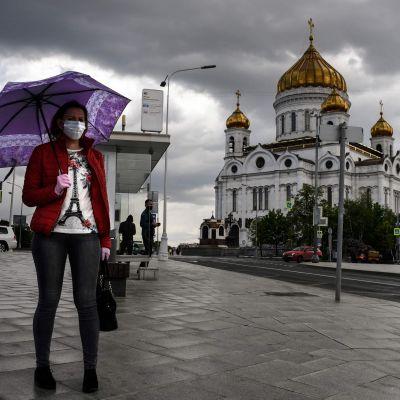 Nainen seisoo maski kasvoillaan Moskovassa Kristus Vapahtajan katedraalin edessä.
