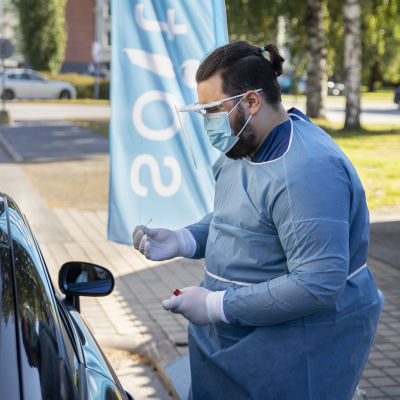 Suojavarusteiseen pukeutunut mies tekee koronatestiä autossa istuvalle ihmiselle.