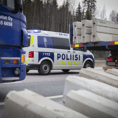 Poliisiauto vahtii liikennettä kun rakennusmiehet asentavat betoniporsaita Valtatie 3. tiesululle  27.3.2020.
