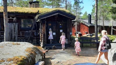 Barn och en kvinna som går mot ett timrat hus.