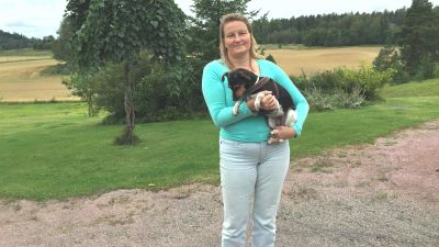Kvinna som håller hund i famnen.