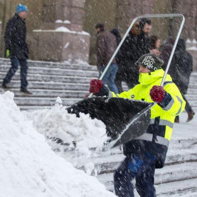 Mies heittää lunta lumikolalla Helsingin päärautatieasemalla.