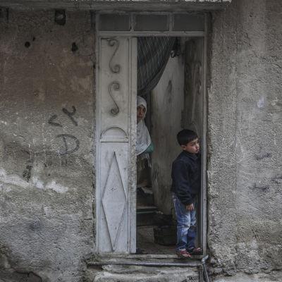 Syriska barnen Yasser och Heba tittar ut från sitt hem i Damaskus i Syrien 22 februari 2016.