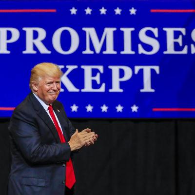"""Donald Trump klappar händerna på ett stormöte i delstaten Iowa. I bakgrunden syns texten """"Promises kept"""", fritt översatt: löften som hålls."""