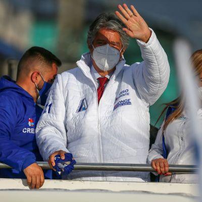 Bild på man i vit jacka som håller upp en hand och vinkar.