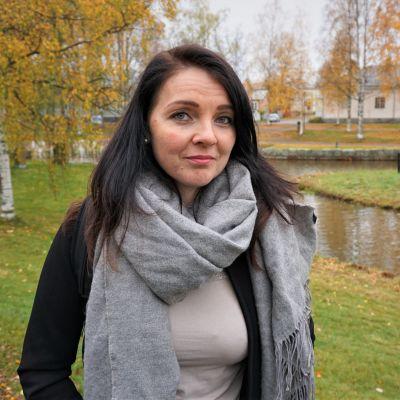 Kvinna i svart jacka står i en park.