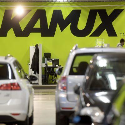 Kamux-autokaupan suuri logo, etualalla myytäviä autoja.