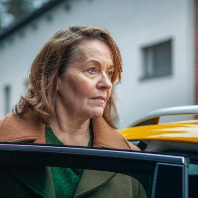Ruskeatukkainen ja -takkinen nainen katsoo auton oven yli.