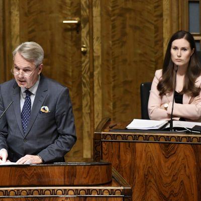 Pekka Haavisto står vid ett podium i riksdagen. I bakgrunden syns statsminister Sanna Marin som har armarna i kors.