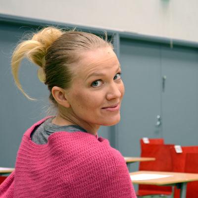 Saana Ruotsala sitter vid en pulpet i salen där studentskrivningarna sker.