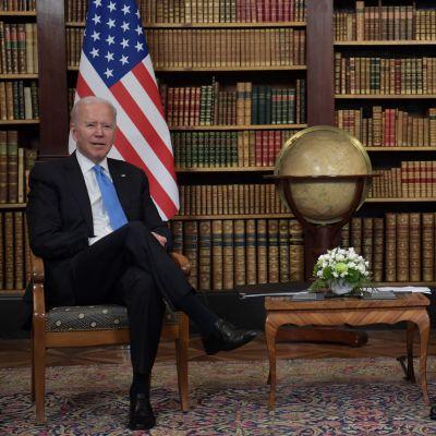Joe Biden ja Vladimir Putin istuvat maidensa lippujen ja kirjahyllyn edessä.