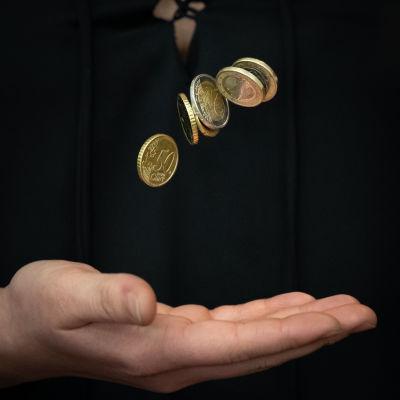 en hand kastar upp mynt i luften mot en svart bakgrund
