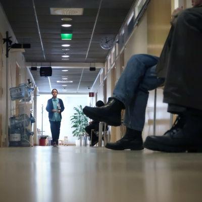 Hoitaja kävelee terveyskeskuksen käytävällä.