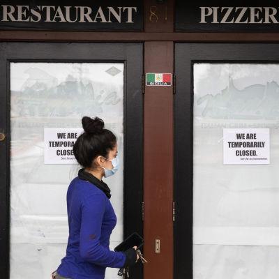 Kasvonsa suojannut nainen ravintolan ovella. Ovessa kerrotaan ravintolan olevan toistaiseksi kiinni.
