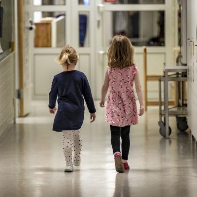 Två unga flickor går i en korridor.