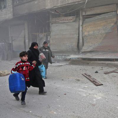 Kvinna med barn söker skydd undan bombardemang i östra Ghouta