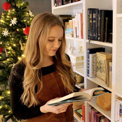 Ung blond kvinna tittar i en bok.