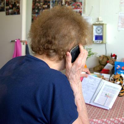 Iäkäs nainen puhuu puhelimessa.