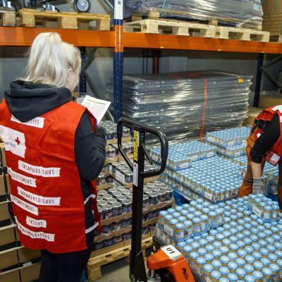 Två frivilligarbete sorterar mathjälp i en lagerlokal i Tammerfors.