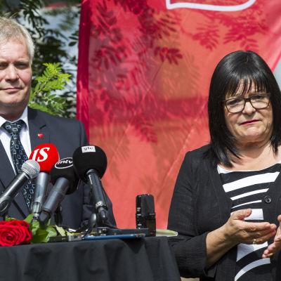 Antti Rinne och Maria Tolppanen vid ett bord med mikrofoner.