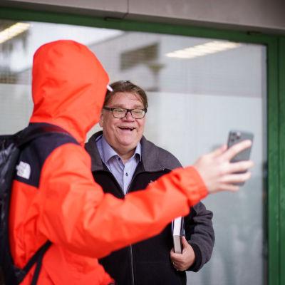 En ung person i orange jacka tar en selfie med Timo Soinin i ett köpcenter i Ivisnäs.