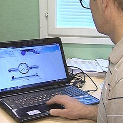Mies testaamassa internet-yhteyden nopeutta kannettavalla tietokoneella.
