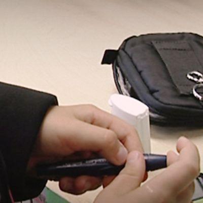 Lapsi mittaa sokeriarvonsa koulupulpetin ääressä.